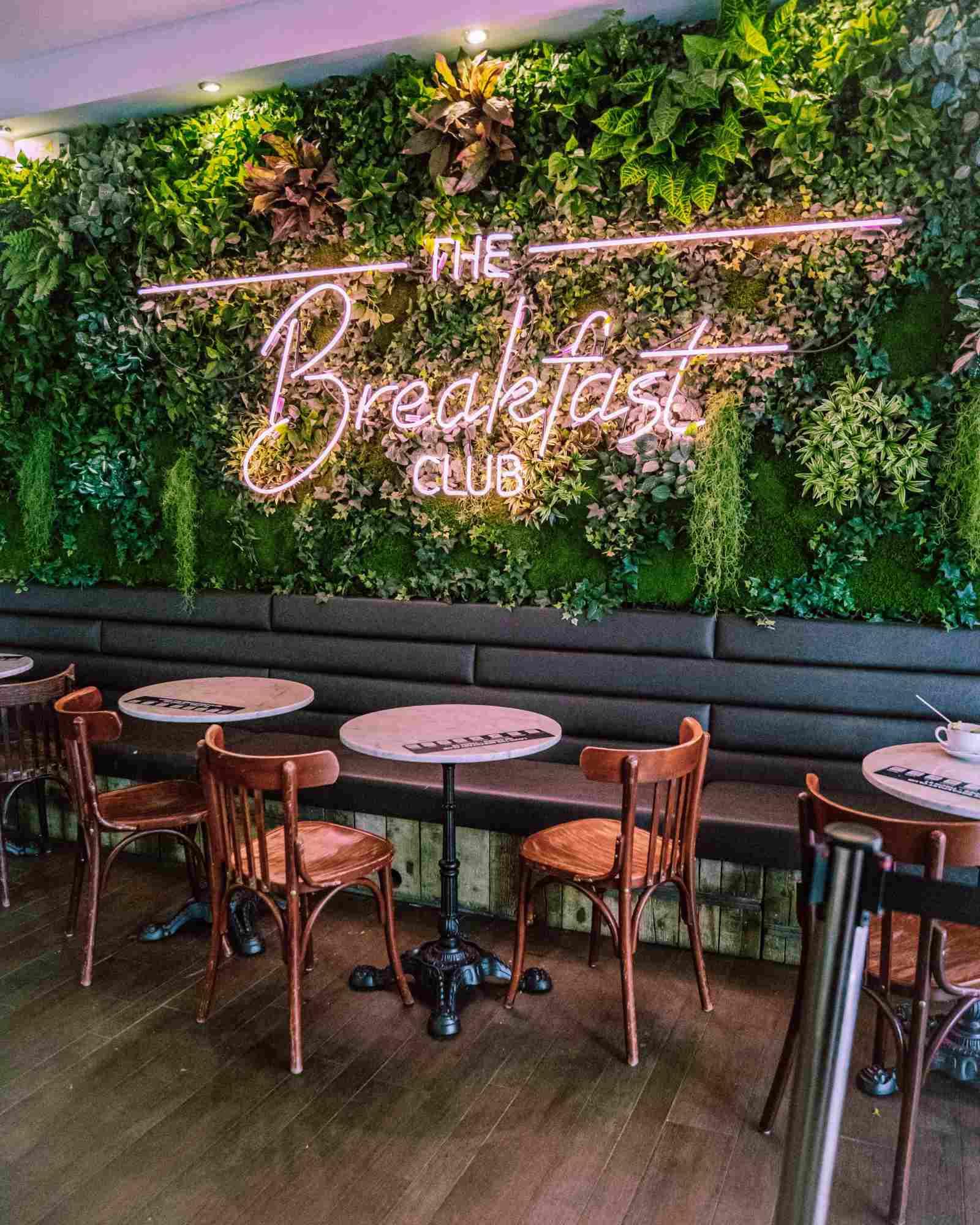 Textilpflanzenwand mit Leuchtschrift im Restaurant